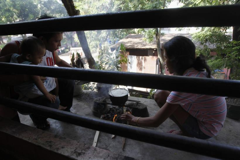 A couple cooks a pot of rice in a school building used as an evacuation center for tropical storm Washi survivors