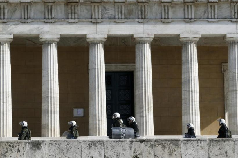 Riot policemen walk in front of the parliament during an anti-austerity rally in Athens February 11, 2012.