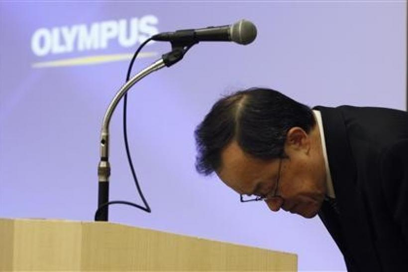 Olympus Corp President Shuichi Takayama bows after speaking at a news conference in Tokyo February 13, 2012. Japan's scandal-hit Olympus Corp on Monday forecast a $410 million full-year net loss due to its ailing camera business and tax asset writedo