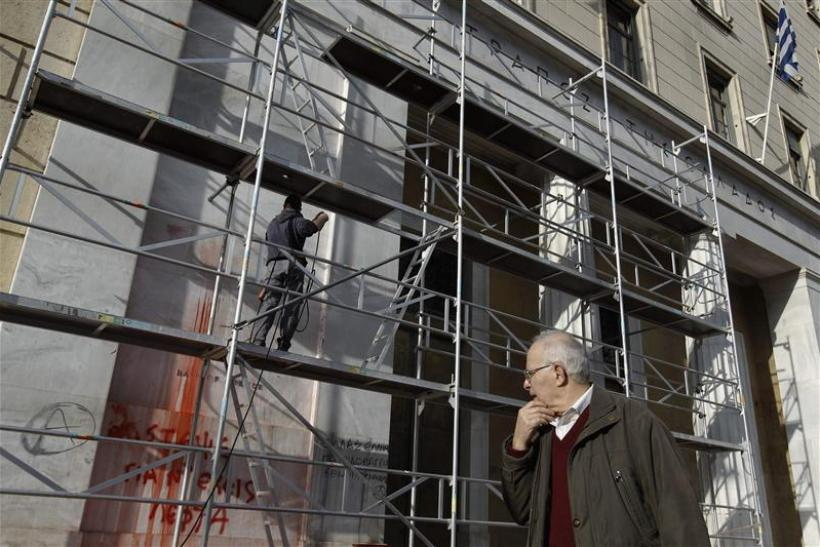 Man walks past Bank of Greece as cleaning works are in progress after Sunday's violent protests in Athens