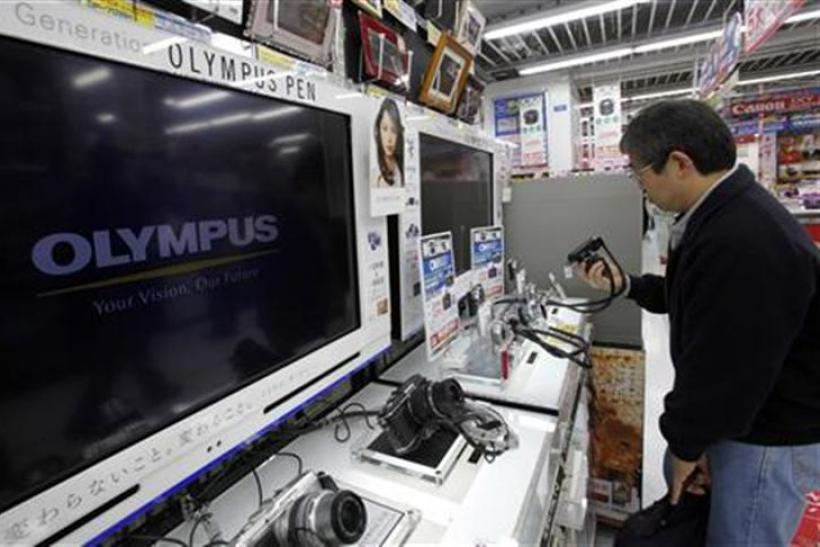 Man looks at Olympus Corp digital cameras at an electronics store in Tokyo