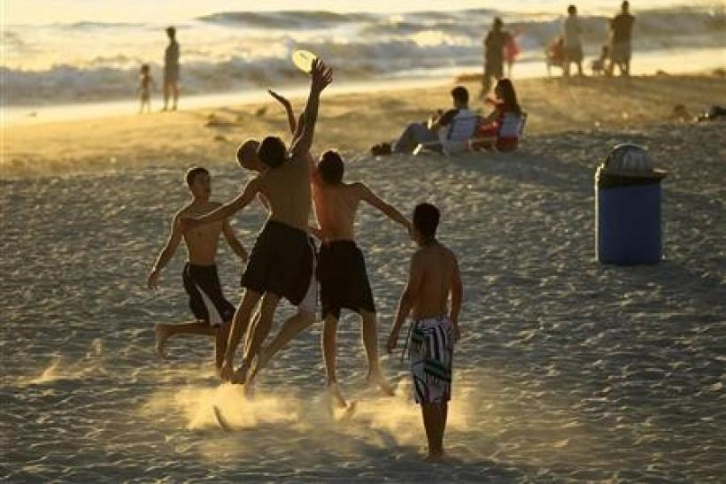 Boys play frisbee in the sand at Moonlight Beach in Encinitas, California