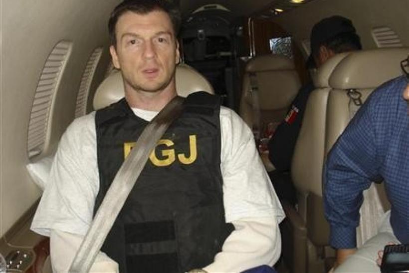Bruce Beresford-Redman (L) sits inside a plane after his arrival in Cancun February 8, 2012 in this handout picture released by the Attorney General's office (PGR)