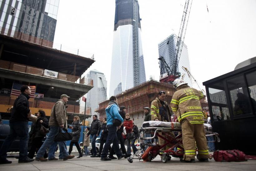Firefighters stand beside an empty stretcher at the World Trade Center construction site in New York