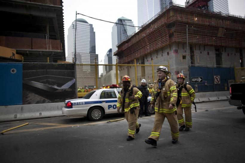 Firefighters walk near the World Trade Center construction site after a large column fell 40 stories in New York