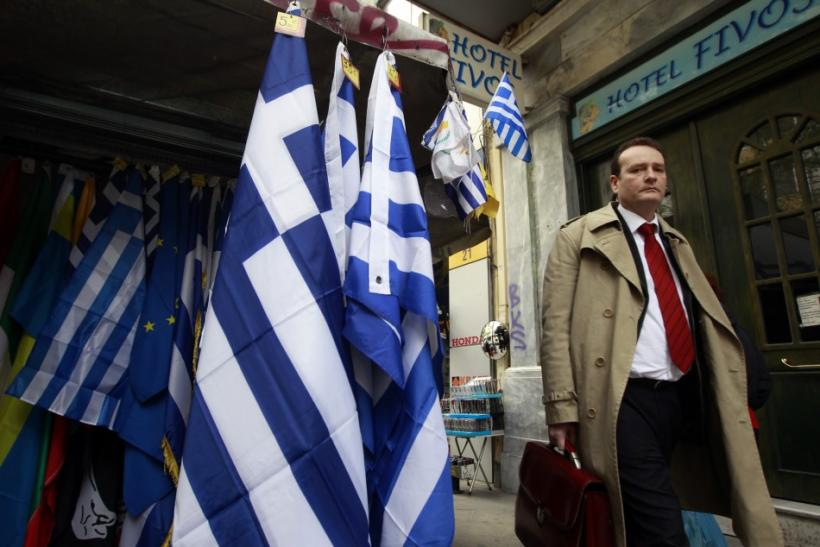 A man walks next to a kiosk selling Greek flags in Athens