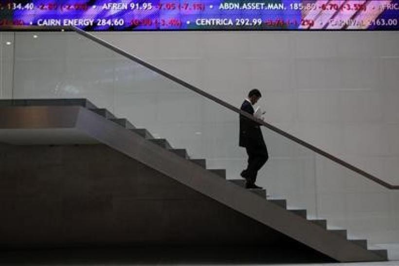 A man walks down steps under a share price ticker at the London Stock Exchange in the City of London November 1, 2011.