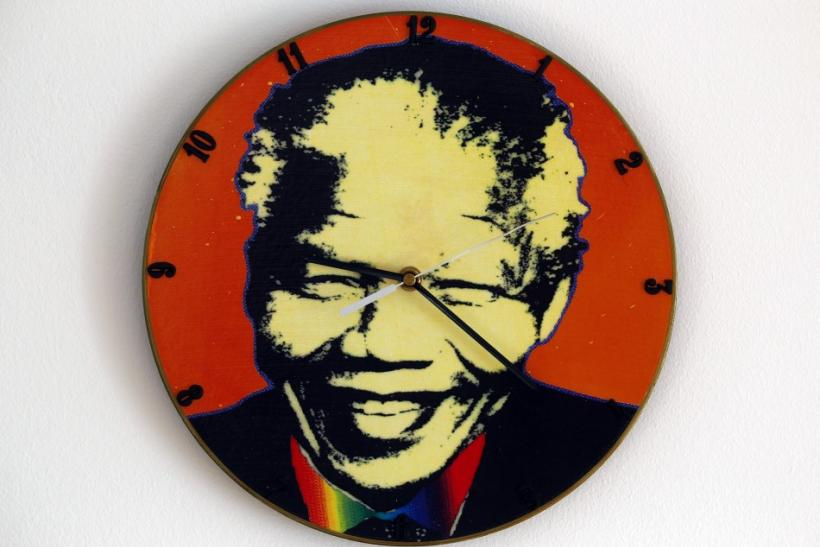 A clock made out of an old vinyl record showing Nelson Mandela's headshot is measuring time in Warsaw February 8, 2012.