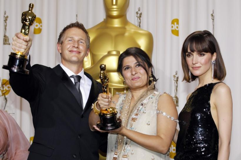 Directors Daniel Junge and Sharmeen Obaid-Chinoy, winners of Best Documentary Short Subject, pose with presenter Rose Byrne backstage during the 84th Academy Awards in Hollywood