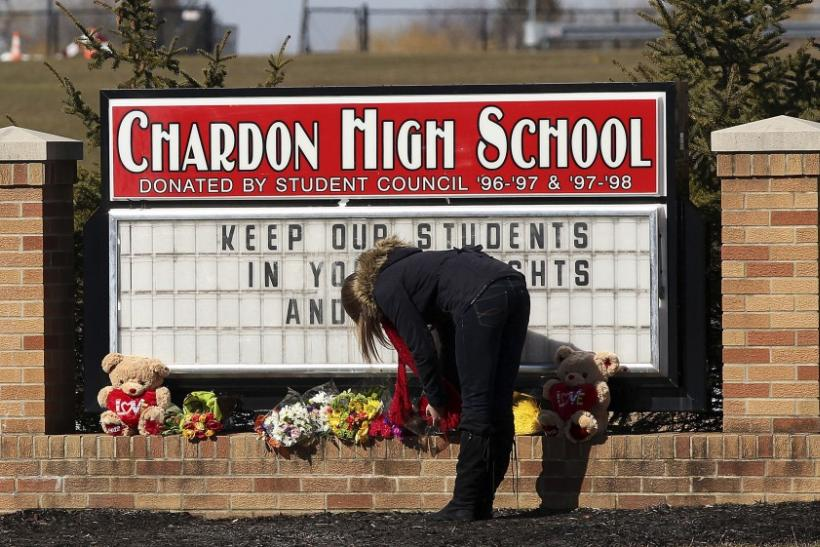 An unidentified female student places a bouquet of roses at the base of the Chardon High School sign in Chardon