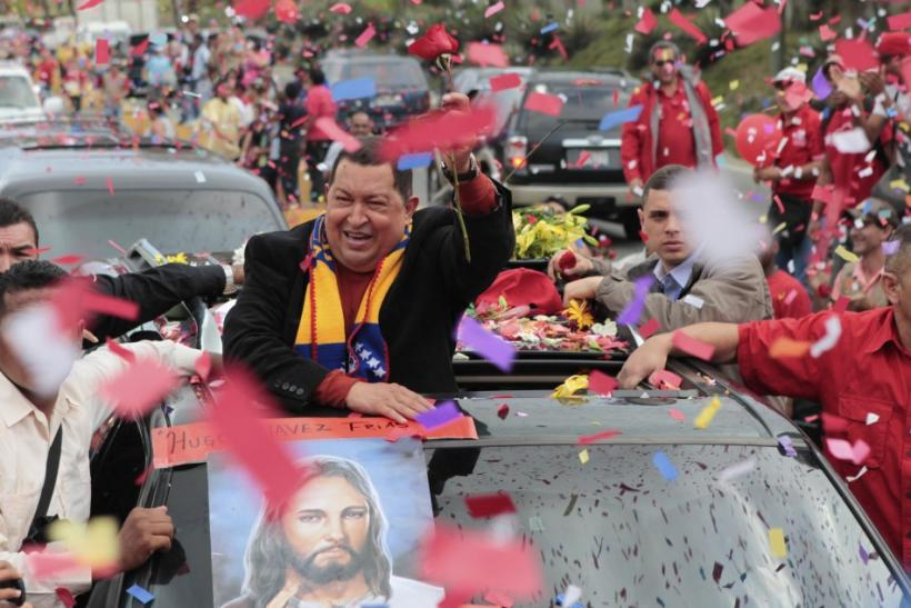 Venezuela's President Hugo Chavez greets supporters on his way to the airport, before his departure to Cuba in Caracas