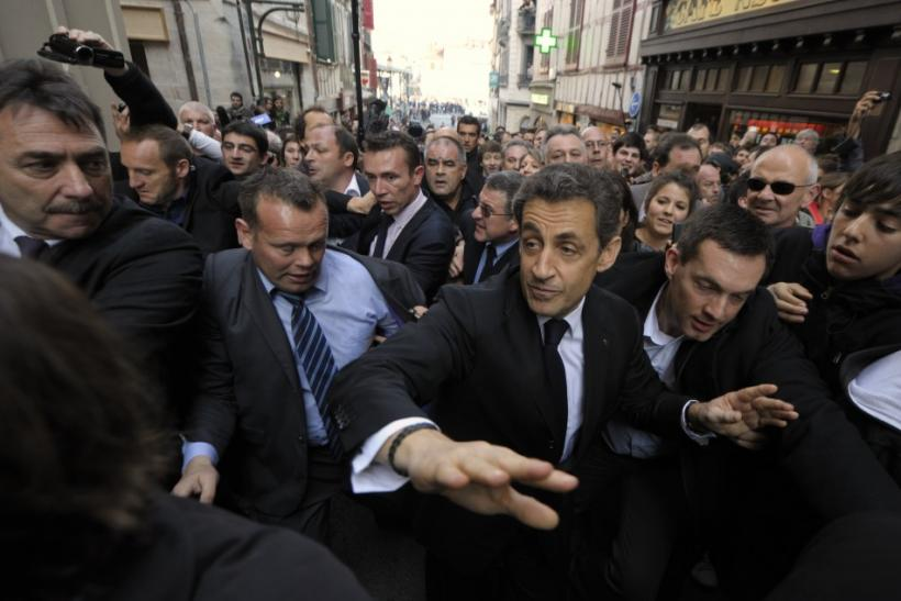 Nicolas Sarkozy, France's President and UMP party candidate for the 2012 French presidential election, walks in the street protected by plain-clothes policemen during a campaign trip in Bayonne.