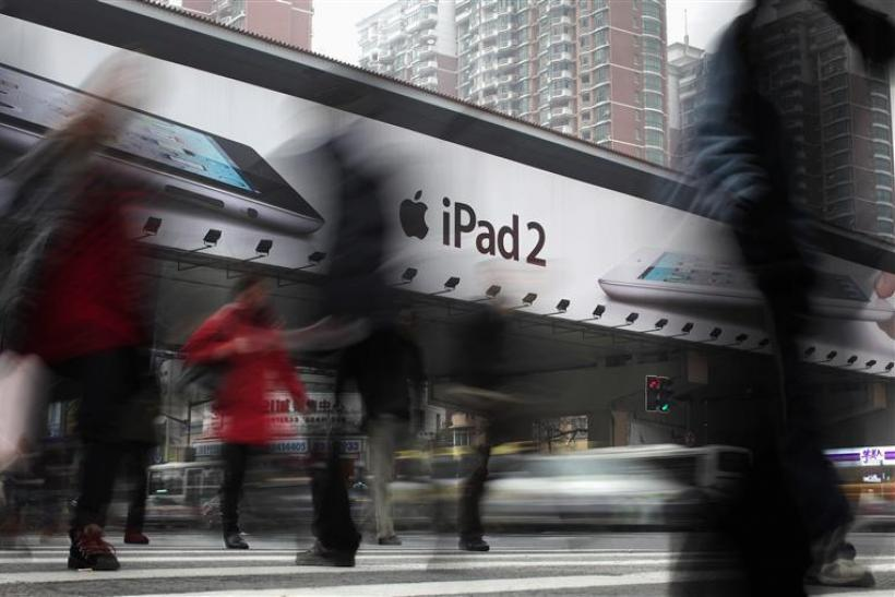 People walk past an Apple billboard advertising the iPad 2 in downtown Shanghai.