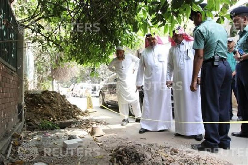 Police and officials from the Saudi Arabian embassy in Bangladesh inspect the spot where Khalaf Al Ali was shot dead in Dhaka