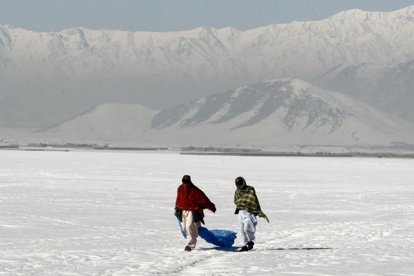 Afghan residents walk on a snow covered field near Bagram highway in Afghanistan