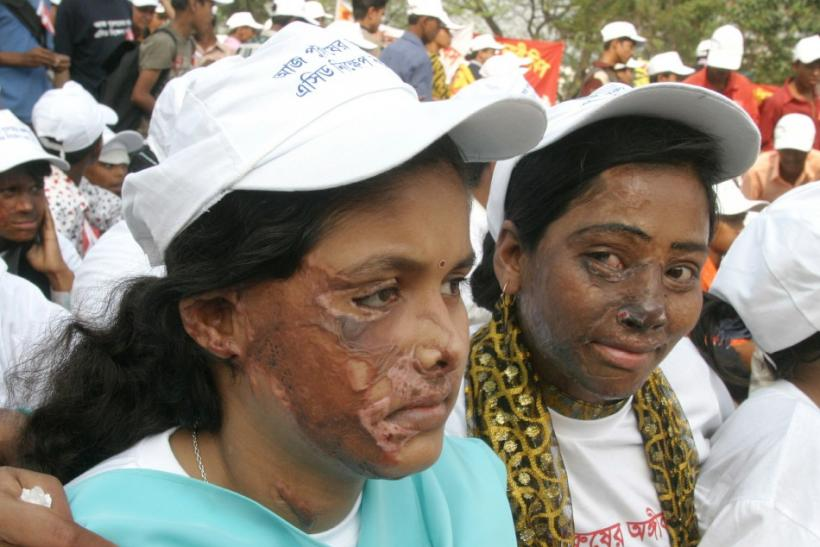 Two Bangladeshi women with faces burned by acid join a rally of thousands of men and women to mark I