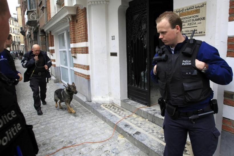 A police officer with a sniffing dog arrives at the Rida mosque which has been set on fire in Anderlecht commune in the west of Brussels