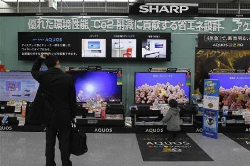 A man looks around Sharp's TV sets at an electronics store in Tokyo February 1, 2012.