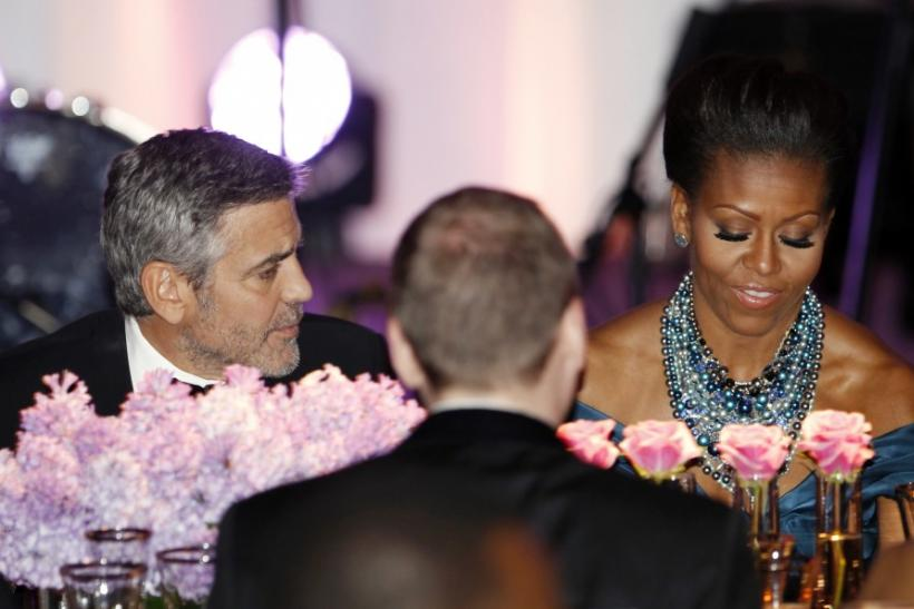 Actor George Clooney sits beside first lady Michelle Obama during the State Dinner for British Prime Minister David Cameron at the White House in Washington March 14, 2012.