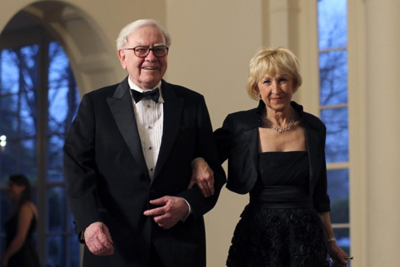 Business magnate Warren Buffett and his wife Astrid Menks arrive for a State Dinner held in honor of Britain's Prime Minister David Cameron and his wife Samantha at the White House in Washington March 14, 2012.