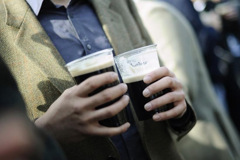 A man drinks two pints of Guinness as he watches the races on Saint Patrick's day at the Cheltenham Festival horse racing meet in Gloucestershire, western England March 17, 2011.