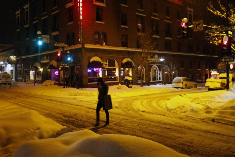 A pedestrian crosses an intersection where several inches of snow have covered the ground in Flagstaff, Arizona, March 18, 2012. The late winter storm kept temperatures well below normal in California on Sunday and generated heavy snow fall in several sta
