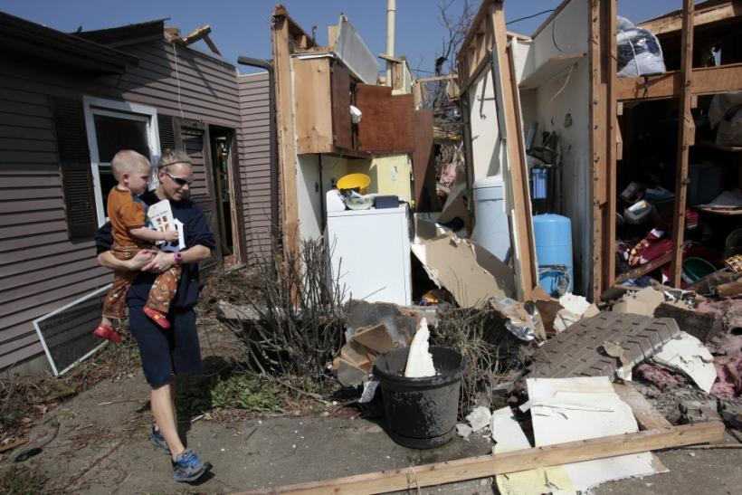 Katie Clifford carries her son as she looks at her home destroyed by a tornado in Dexter, Michigan, March 16, 2012.
