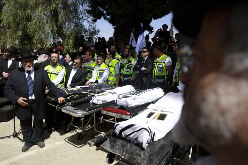 People stand around the bodies of victims of Monday's shooting in Toulouse, during their joint funeral service in Jerusalem