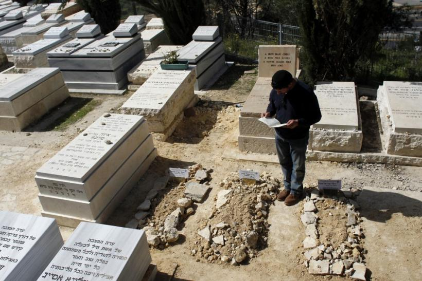 A mourner stands over the fresh graves of victims of Monday's shooting in Toulouse, after their joint funeral in Jerusalem