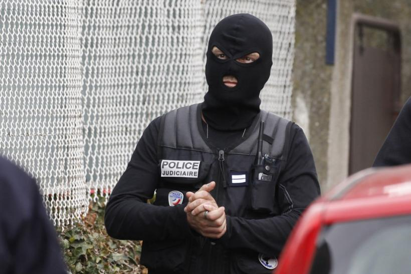 A masked French special unit policeman arrives during a raid on a house to arrest suspects in the killings of three children and a rabbi on Monday at a Jewish school, in Toulouse