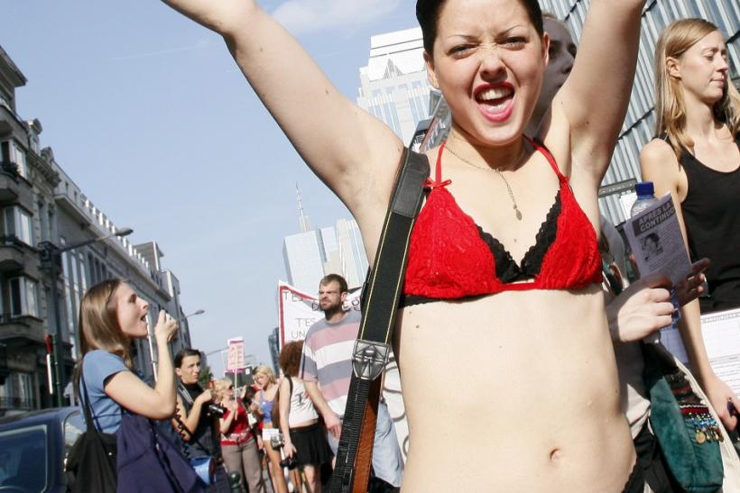 A woman holds up a sign during a SlutWalk rally against sexual abuse and inequality in Brussels