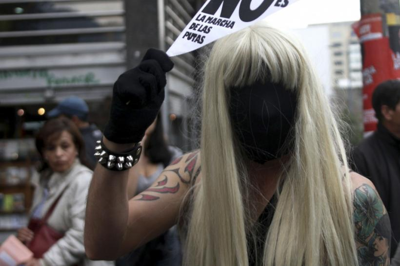 "Man in a wig and mask takes part in a ""March of the whores"" to protest against discrimination and violence against women in Bogota"