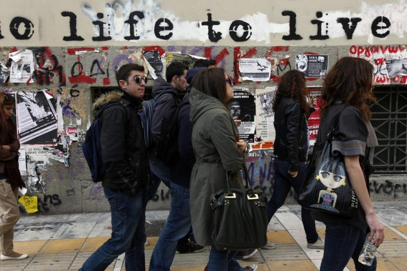 Students walk past graffiti painted on the wall of a building in central Athens March 15, 2012.