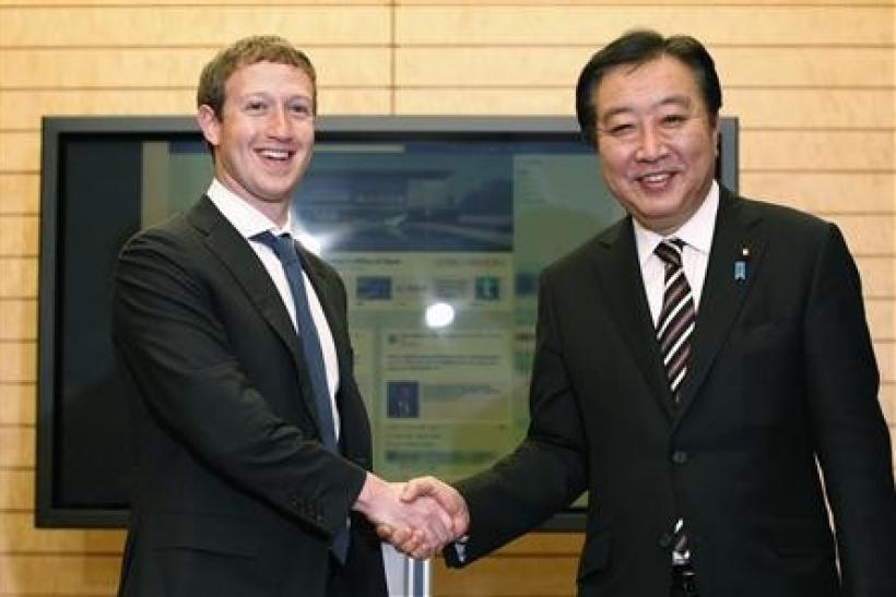 Facebook CEO Mark Zuckerberg (L) shakes hands with Japan's Prime Minister Yoshihiko Noda in front of a monitor displaying a facebook page of the Prime Minister's Office of Japan as they meet at the latter's official residence in Tokyo March