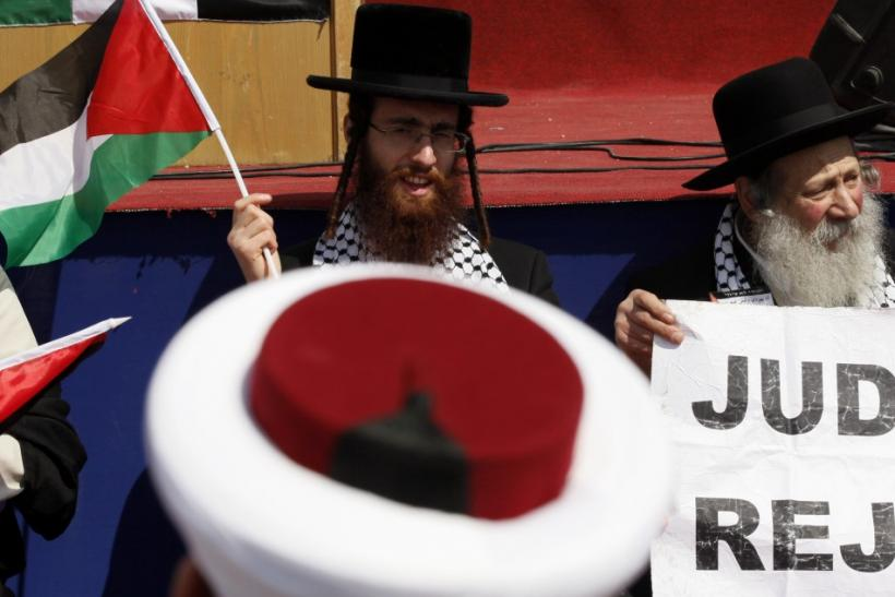 """Delegate of Neturei Karta waves a Palestinian flag at rally in solidarity with Hezbollah and Palestinian factions for a """"Global March to Jerusalem"""" to mark Land Day in Arnoun village"""