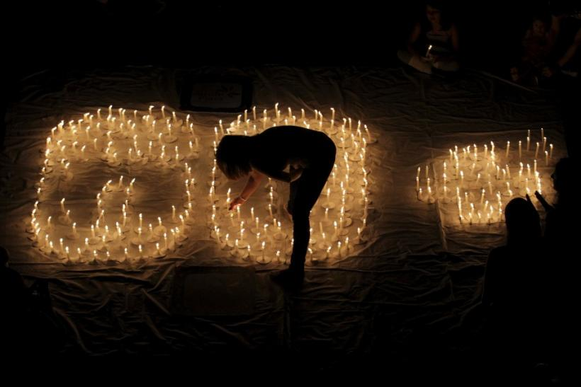 People light candles during Earth Hour after lights were turned off in Cali March 31, 2012. Lights started going off around the world on Saturday in a show of support for renewable energy.