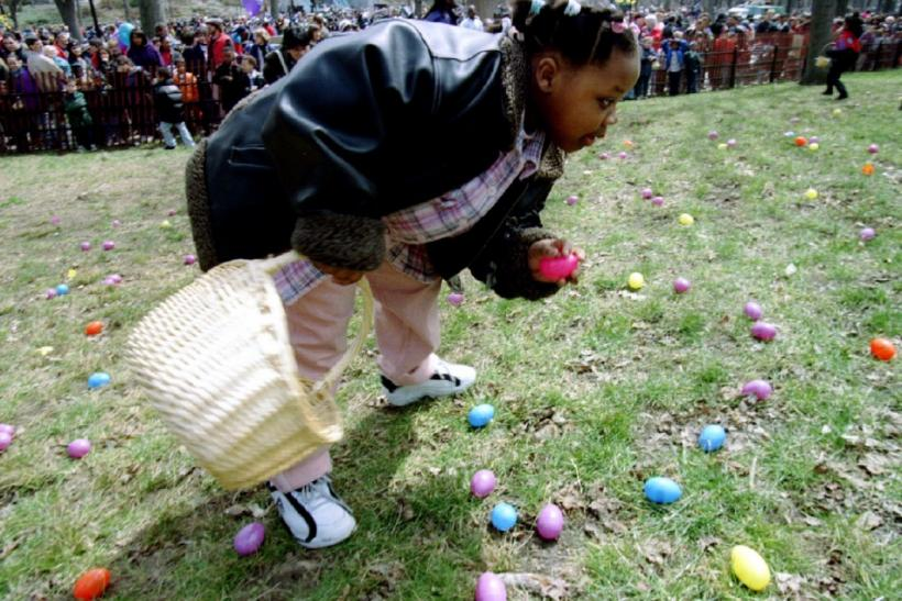 "Keesha Watson of Manhattan collects easter eggs in New York's Central Park, April 6, during the egg hunt at the 50th annual ""Eggstavaganza"" pre-Easter family celebration."