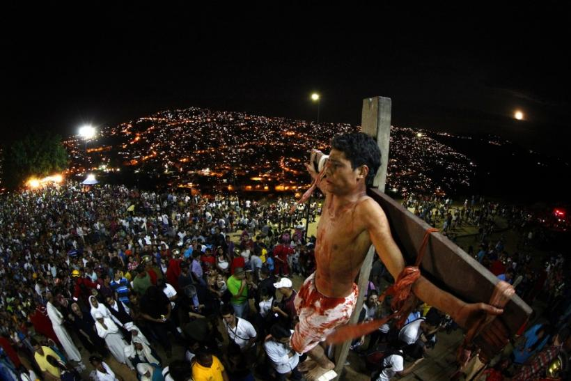 An actor is seen on the cross in a re-enactment of the crucifixion of Jesus Christ on Good Friday in Caracas' biggest slum of Petare April 6, 2012.
