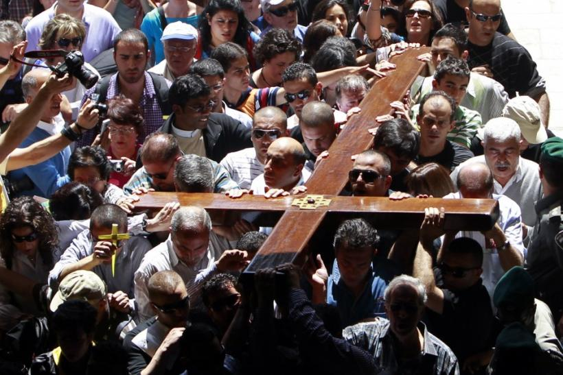 Arab Christian worshippers hold a cross as they enter the Church of the Holy Sepulchre during a procession on Good Friday in Jerusalem's Old City April 6, 2012. Christian worshippers retraced the route Jesus took along Via Dolorosa to his crucifixion in t