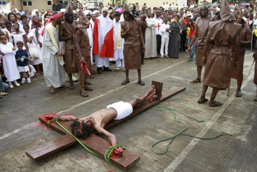 People watch as a man dressed as Jesus Christ is mounted on a cross in front of a Catholic church during a ritual to mark the death of Christ on Good Friday in Nigeria's commercial capital Lagos April 6, 2012.