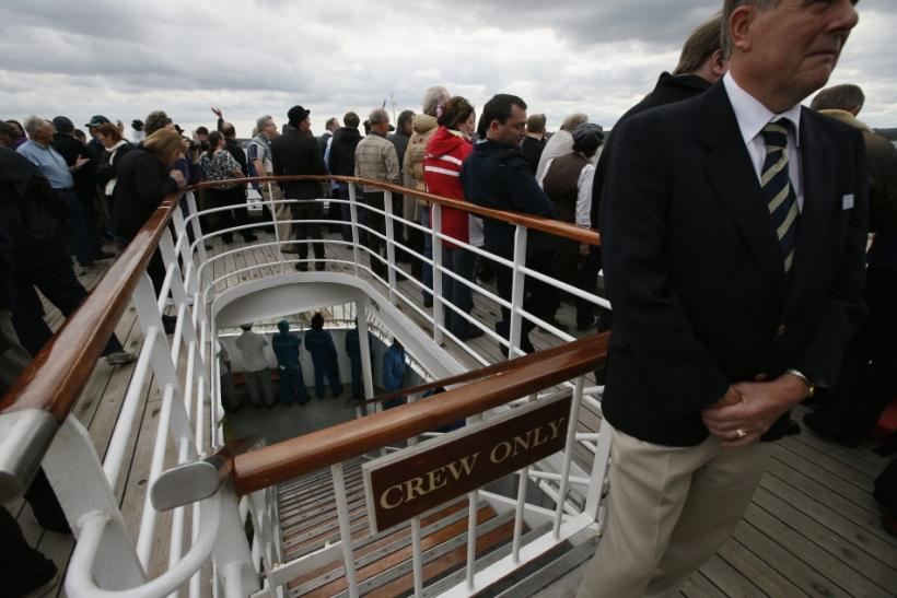 Members of the crew are seen at the deck below partying guests as the Titanic Memorial Cruise leaves port in Southampton