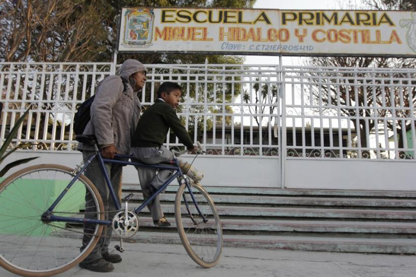 A man and his son stand outside a closed school in San Nicolas de los Ranchos
