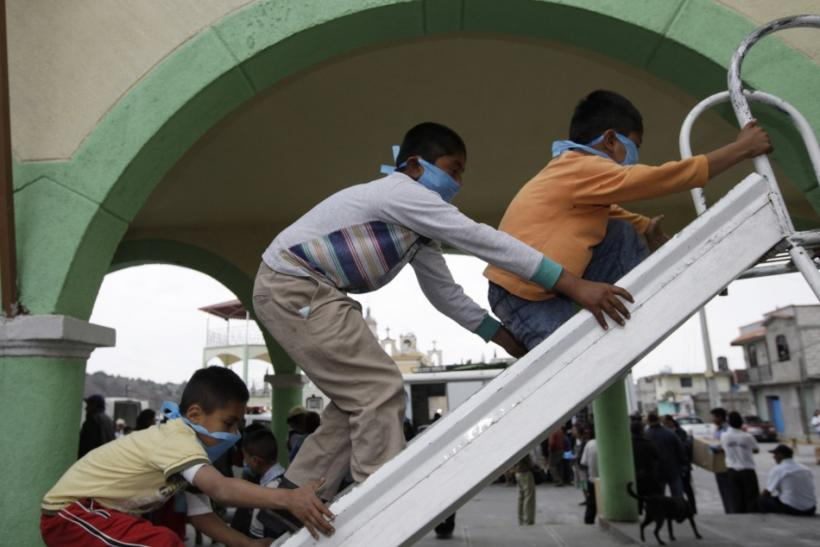 Children wearing surgical masks play on a slide in San Nicolas de los Ranchos