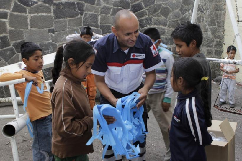 A Red Cross worker hands out surgical masks to children in San Nicolas de los Ranchos