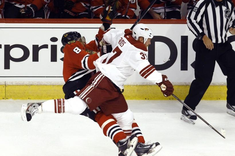Phoenix's Raffi Torres crunches Chicago's Marian Hossa Tuesday night.