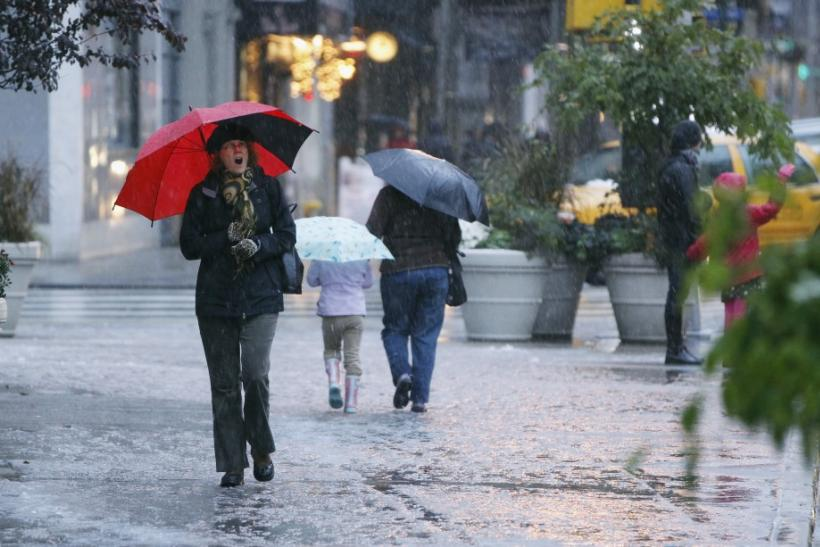 Pedestrians walk through a snow flurry during an early snow storm in New York October 29, 2011. A