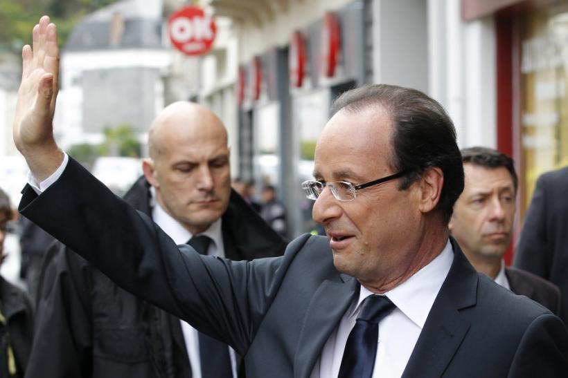 Hollande, Socialist Party candidate for the 2012 French presidential election waves as he arrives at a polling station in Tulle