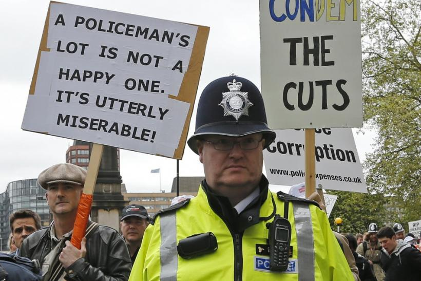 A policeman keeps watch on off-duty police officers as they march in protest at funding cuts through central London