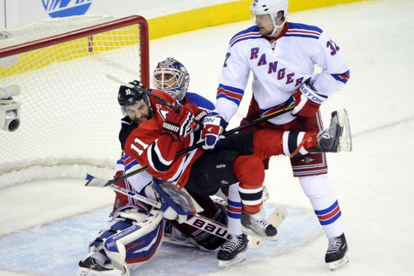 Rangers' Stralman upends Devils' Gionta in front of Rangers' Lundqvist during the third period in game 3 of their NHL Eastern Conference Final hockey playoff game