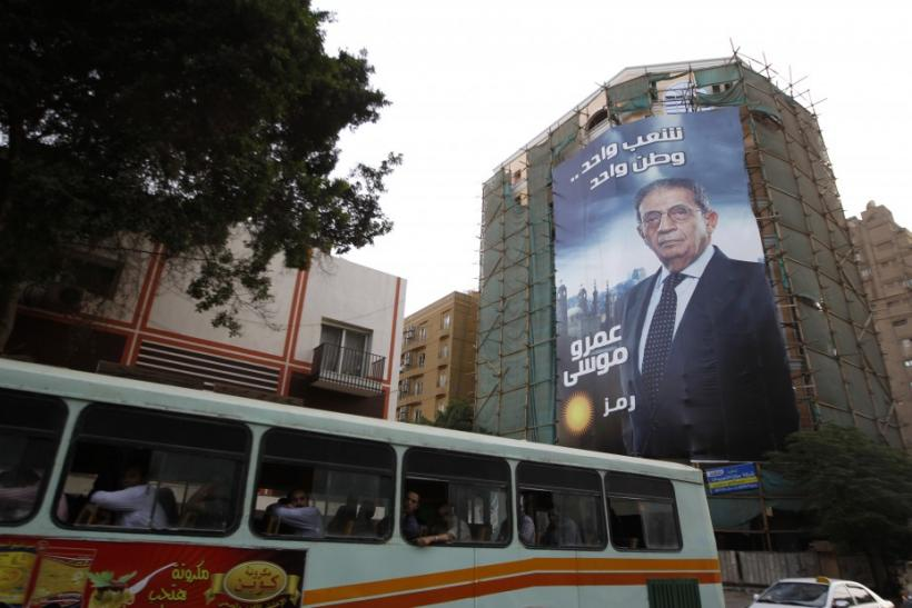 A bus passes by a giant campaign poster of presidential candidate Amr Moussa in Cairo